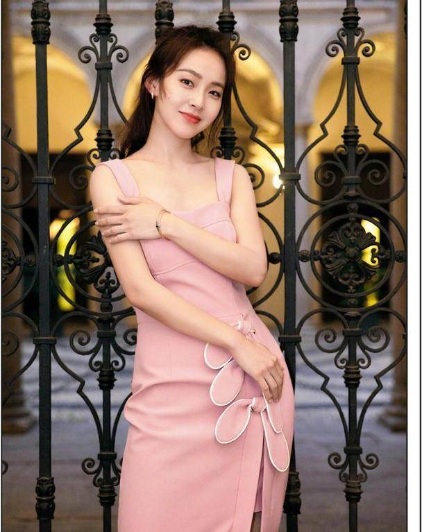 粉红少女张佳宁身穿粉色背带裙,拈花一笑温婉大方,少女感满分
