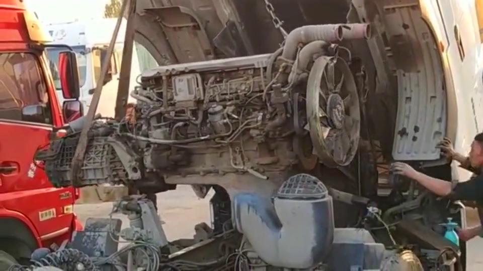 吊车吊一个汽车发动机,机油一撒,旁边汽修工吓了一跳!