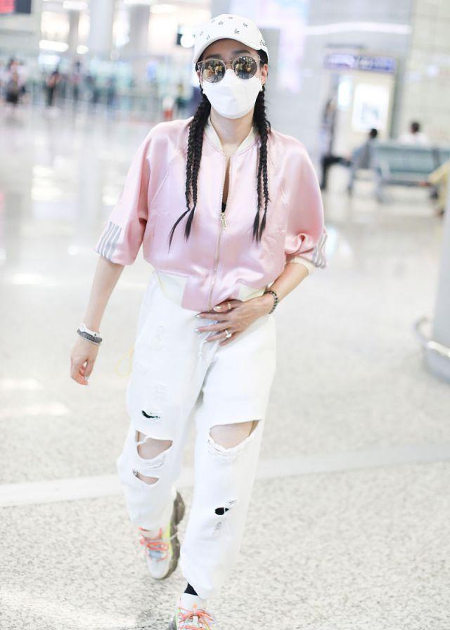 钟丽缇穿粉色阿迪达斯运动衣搭配破洞裤,凌空跃起,变身活力少女