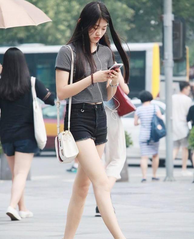 身材窈窕的小姐姐,一件条纹上衣搭配黑色短裤,长发飘飘真迷人