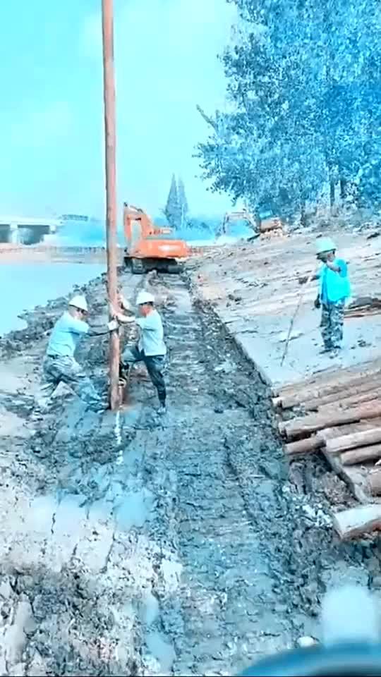 要把木桩锤进泥巴里工人们正一筹莫展时我开着挖掘机就过来了