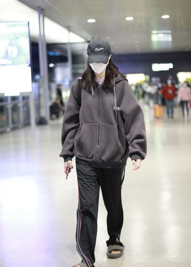 钟楚曦机场昂首阔步脚踩拖鞋超随性,卫衣配条纹裤休闲时髦