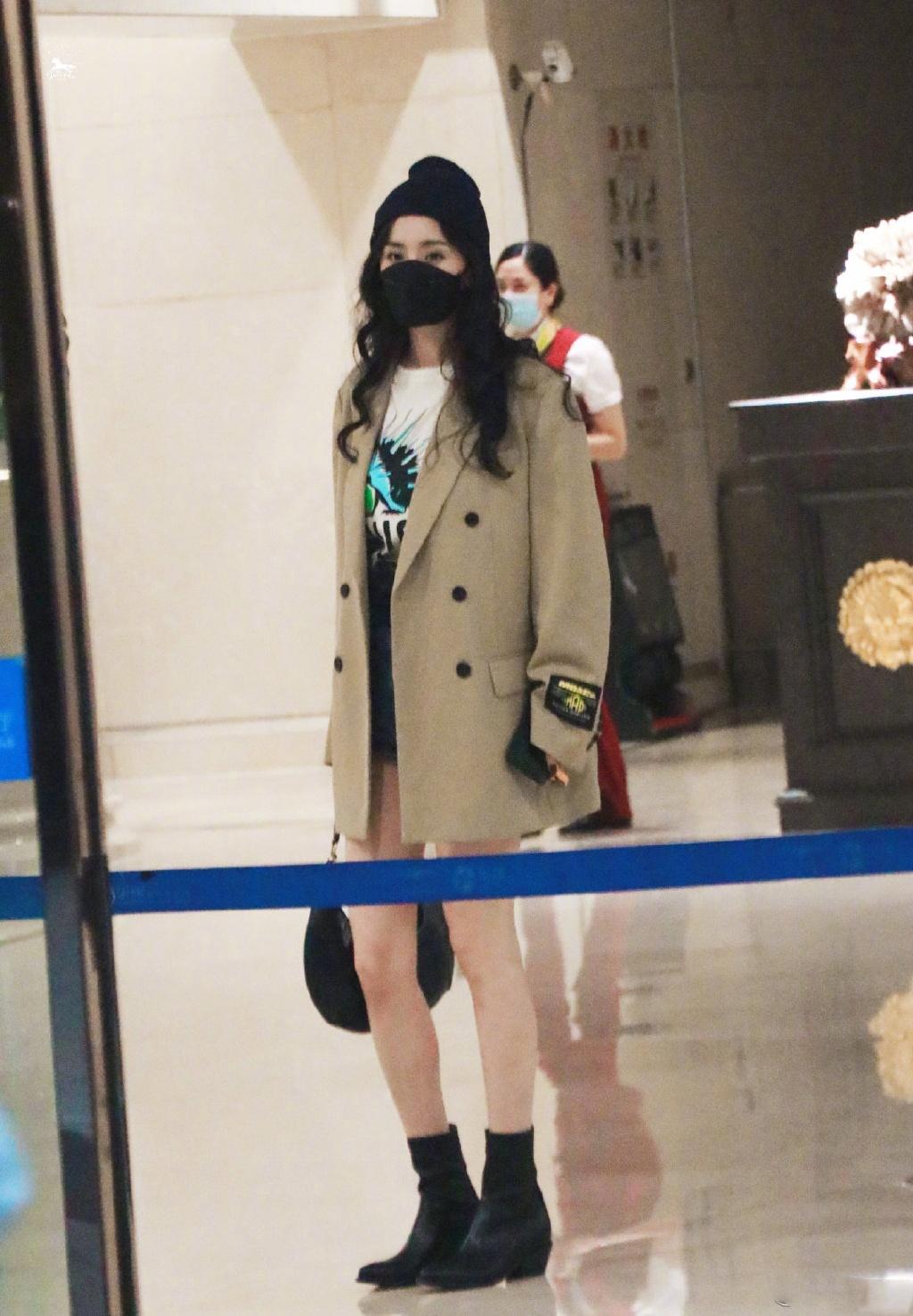 杨幂的机场私服,身着卡其色风衣搭配白T与牛仔短裤