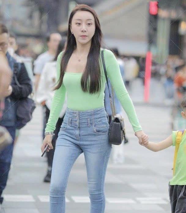 复古牛仔裤搭配亮绿色紧身上衣,颜色打造的清爽感凸显高级气质