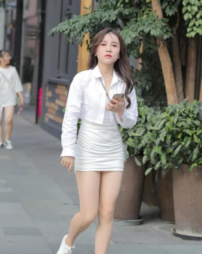 街拍:身穿白色连衣包臀裙搭开衫,小姐姐这个傲娇的小表情