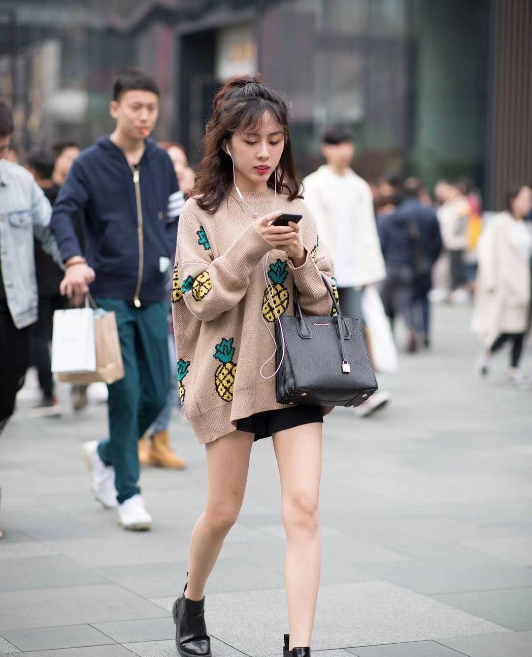 街拍:小姐姐棕色宽松印花毛衣搭配黑色短裤,可爱甜美长腿吸睛