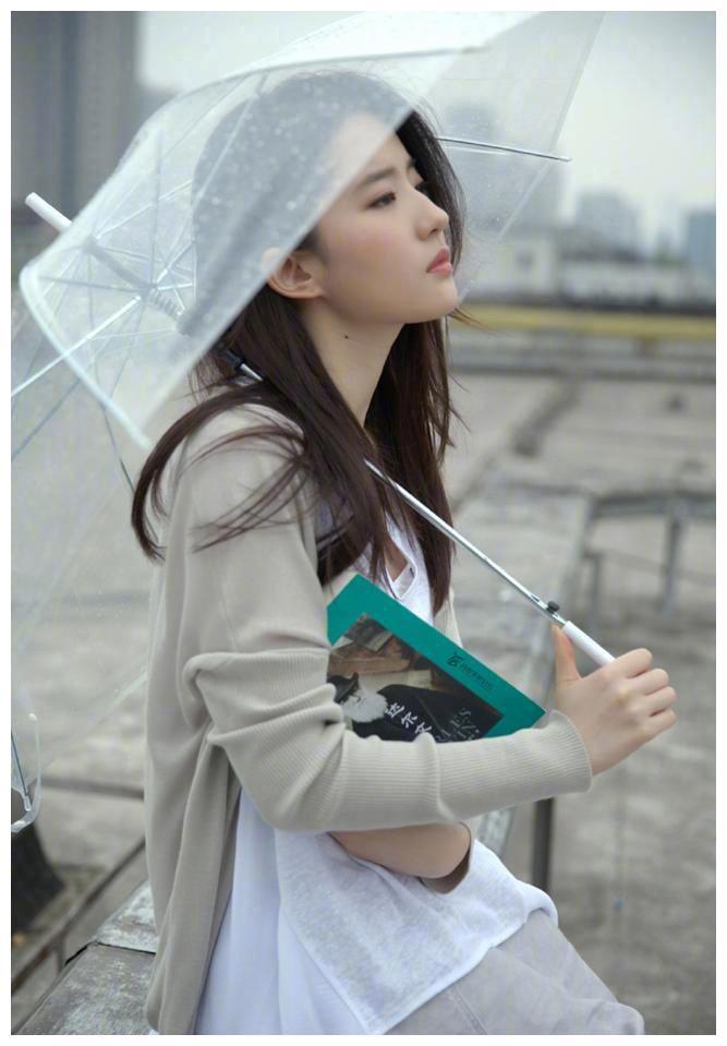 刘亦菲一身灰调宽松造型舒适简约,撑伞捧书妥妥的文艺女神