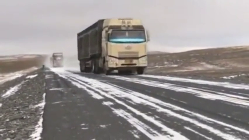 重卡车队通过青藏公路上的无人区,冰雪路面上高速奔驰