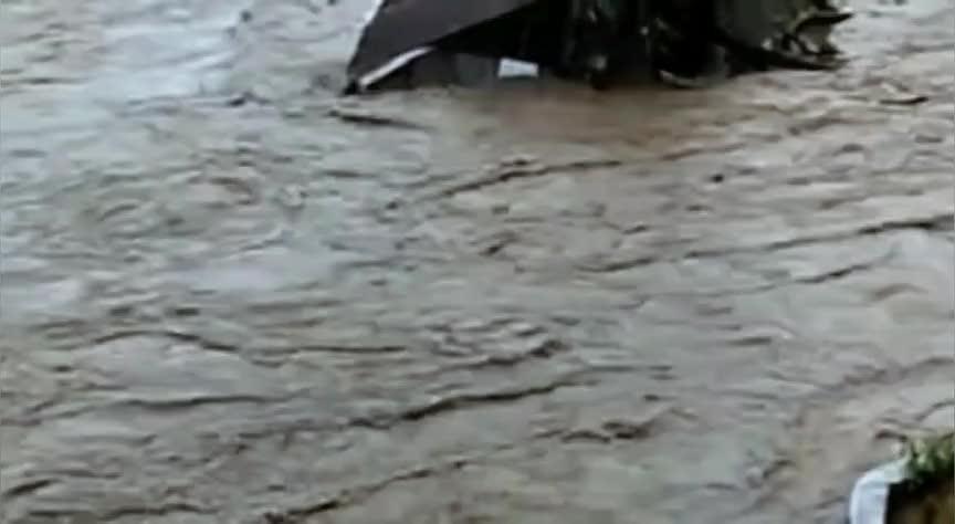 洪水汹涌澎湃,房屋从大桥底下穿过