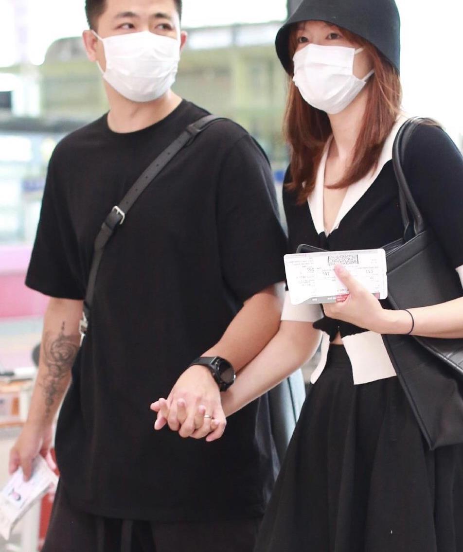 李艾和老公现身机场,穿短袖上衣配A字摆的黑色半身裙,简约高级