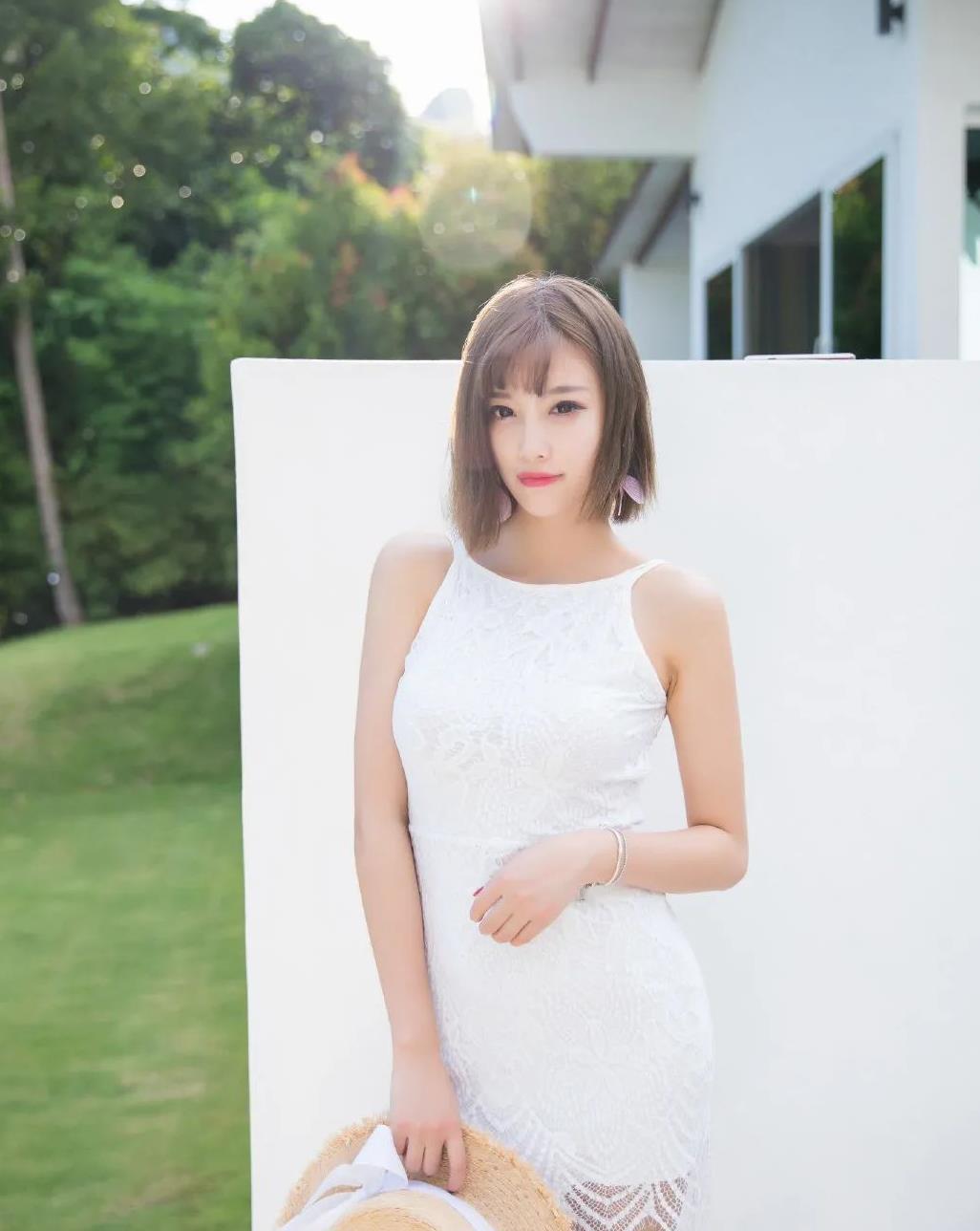 白色吊带连衣短裙搭配时尚礼帽的性感女生