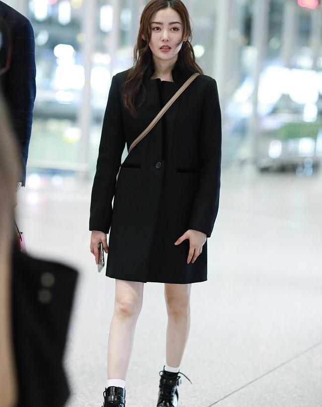 张天爱街拍:黑色大衣裙驼色手袋马丁靴 酷范儿美少女