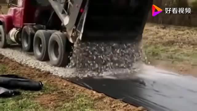 这一看就是一位老司机了,就只是把石子倒在地上,马路就铺好了!