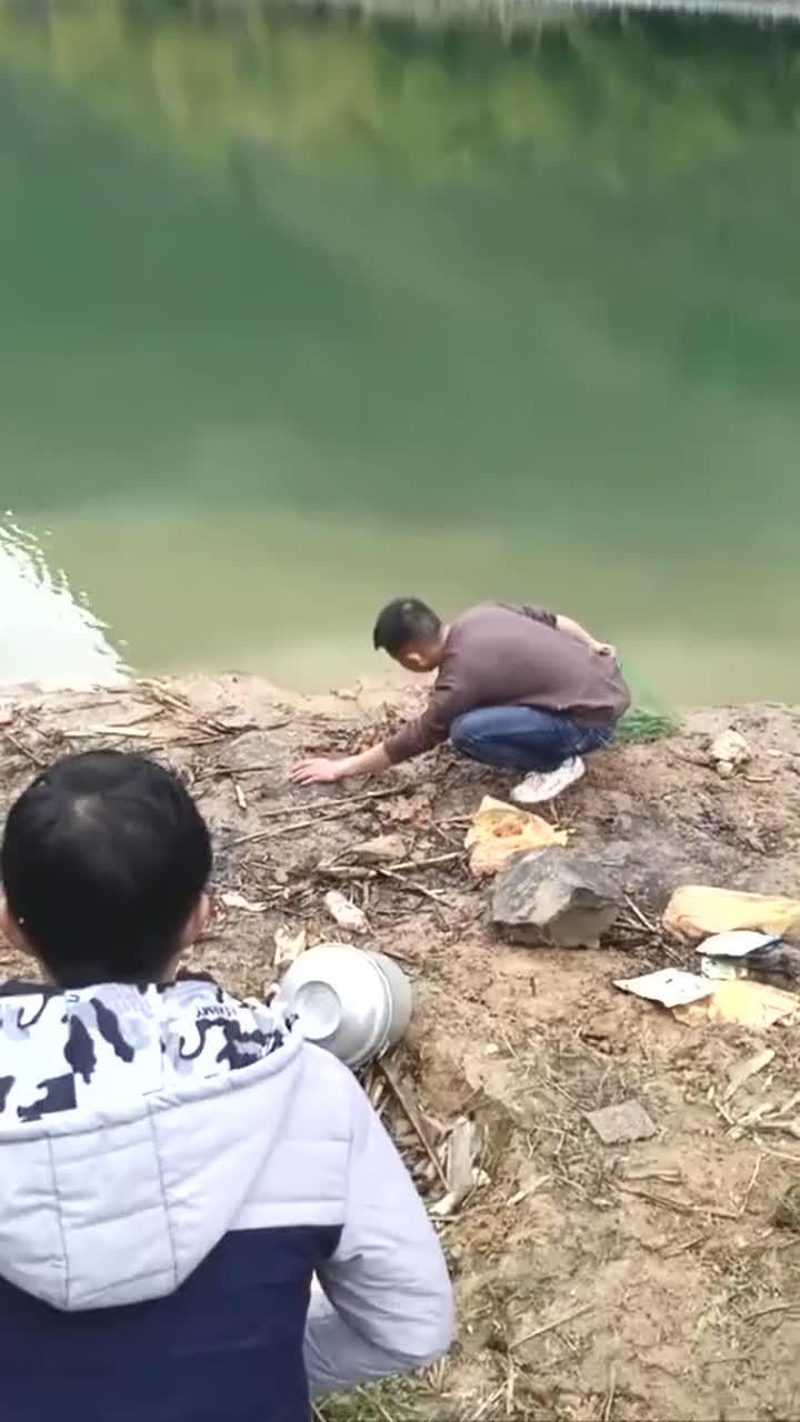 河边抓鱼的小伙,轻轻一捞就这么多鱼,这也太好抓了!