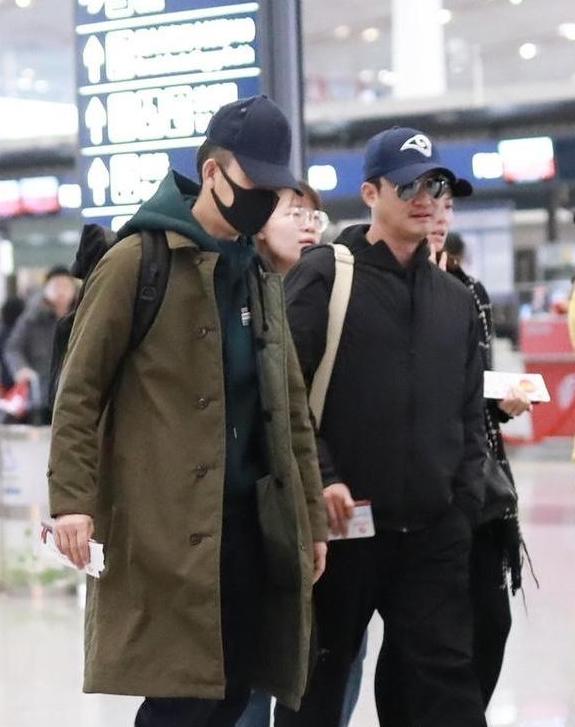 吴京张译同走机场,同戴藏青色帽子默契十足,演绎棉服的时尚穿法