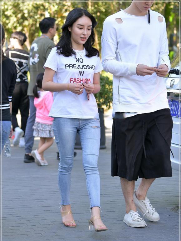 美丽修身的破洞牛仔裤,搭配白色T恤,穿出了简约又迷人的背影