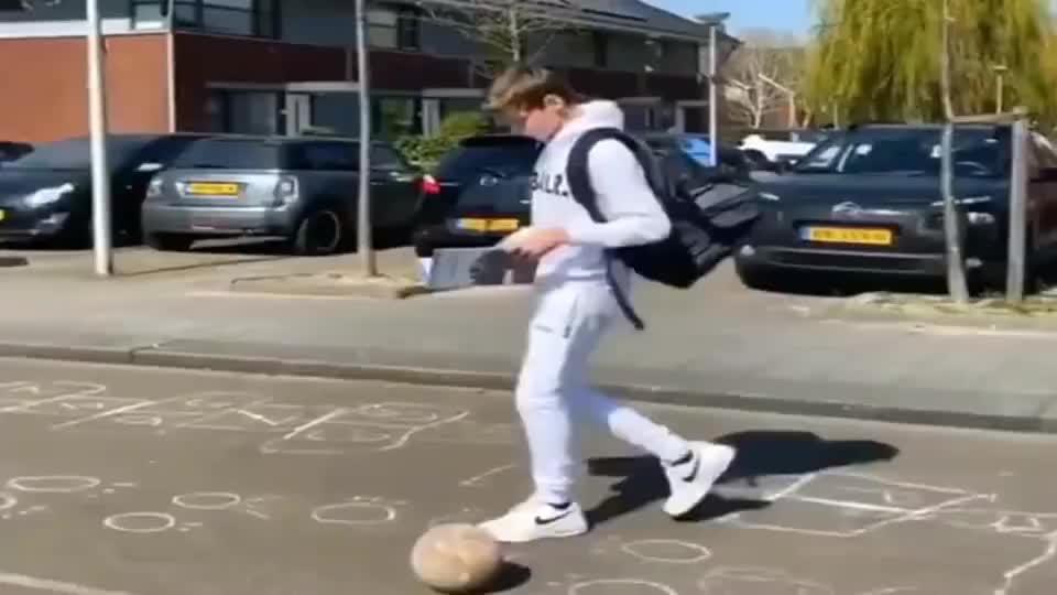 美国小哥哥看报纸,不影响脚下踢球,一个技巧把足球踢进书包里!