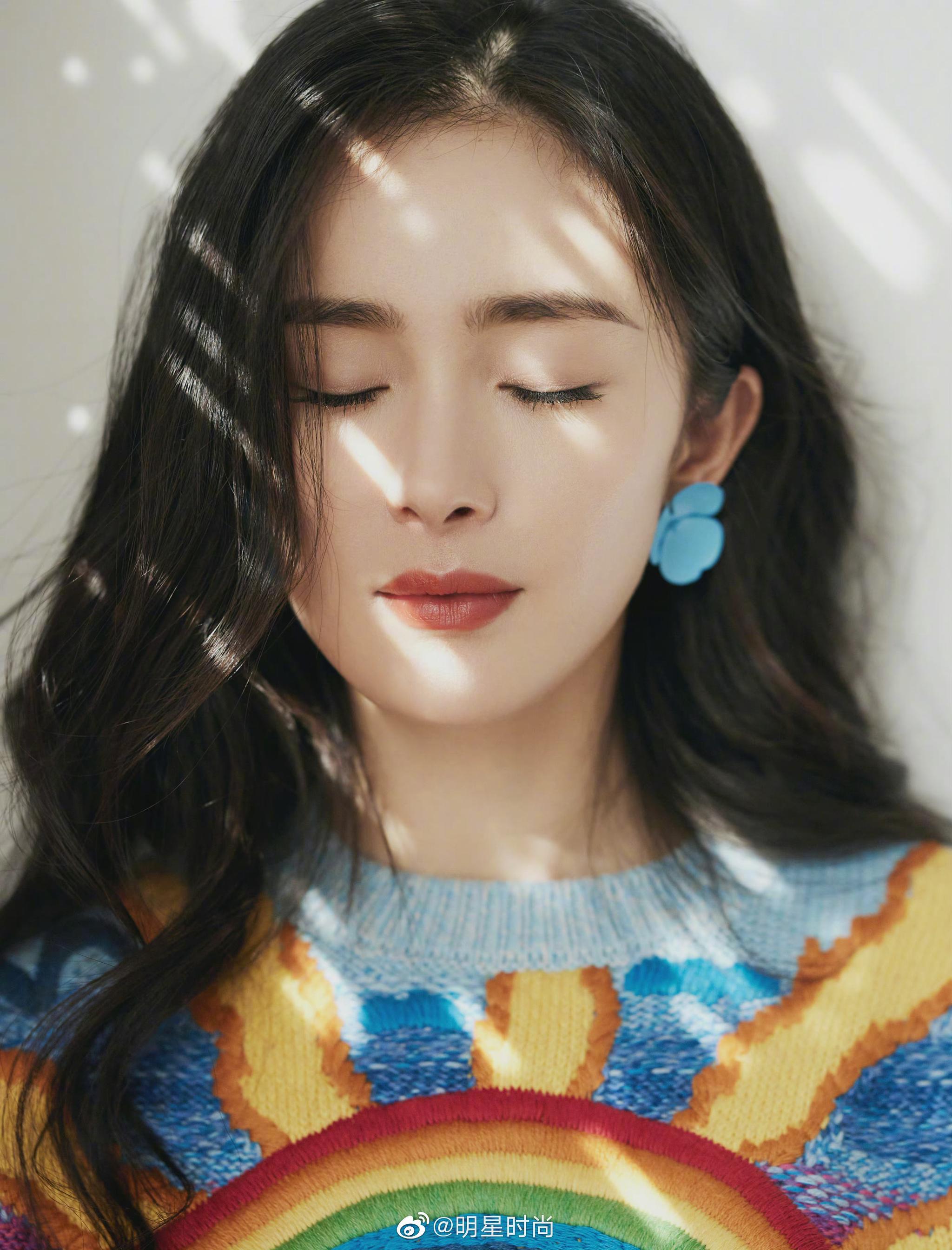 杨幂最新造型,她身着彩虹毛衣搭配蓝色短裙