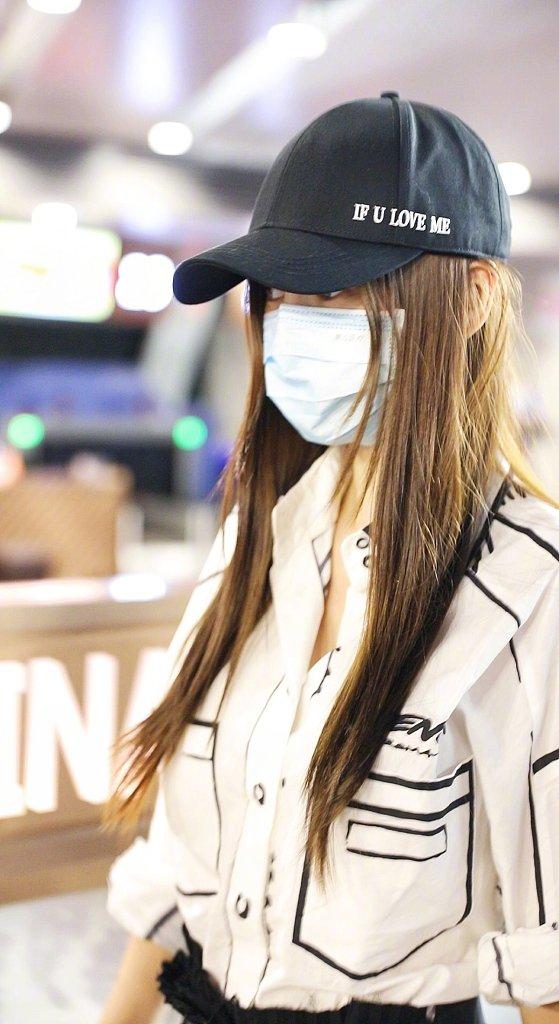 Angelababy现身机场,白色涂鸦衬衫搭配黑色百褶裙
