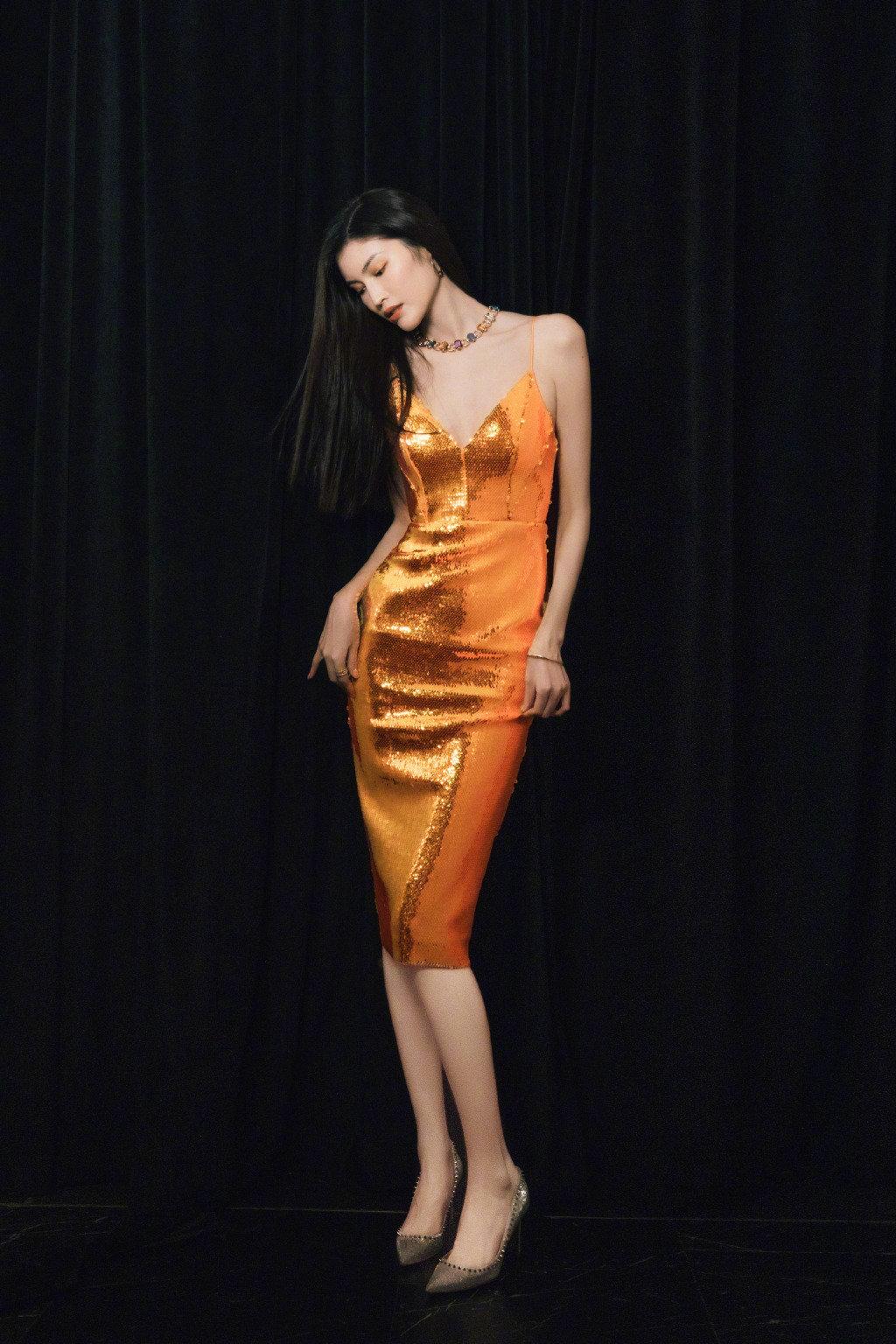 何穗一袭Alex Perry橙色亮片裙,佩戴着宝格丽彩色宝石项链