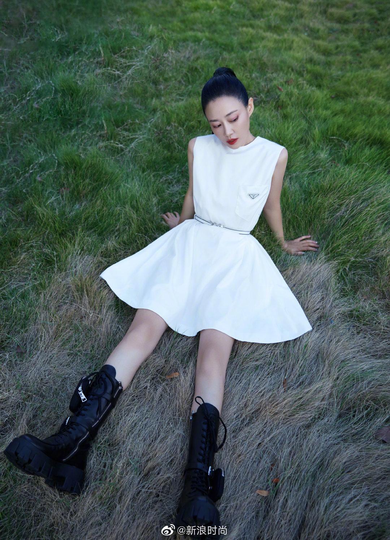 出席活动,一身白色连衣短裙搭配黑色中筒靴,头扎利落的高马尾