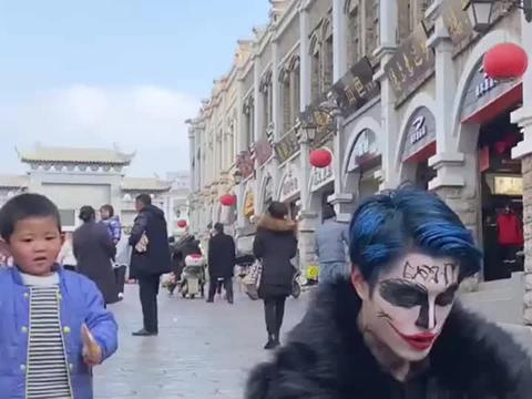 小丑在街边吃饭,孩子送他一只棒棒糖,他的举动让孩子非常暖心!