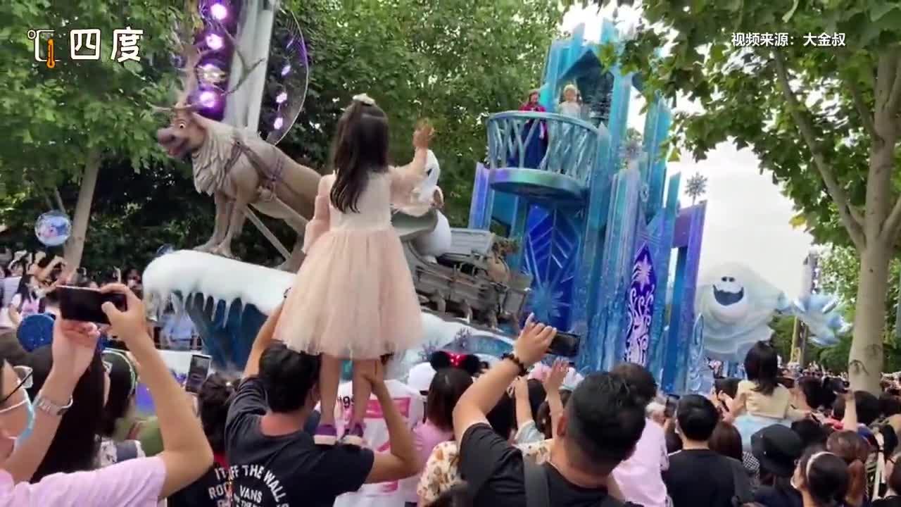 爸爸把女儿扛在肩上看迪士尼花车巡游 全程保持一个姿势没动过