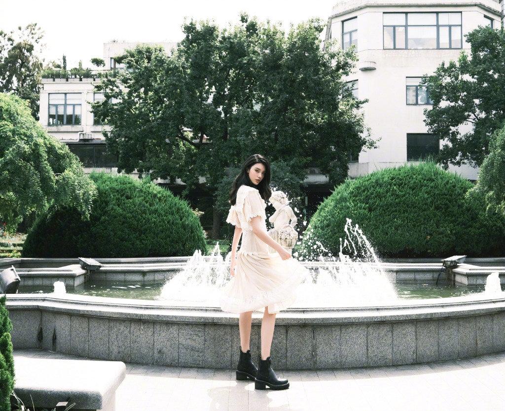 奚梦瑶身着米色刺绣百褶裙搭配马丁靴,利落简洁的优雅格调