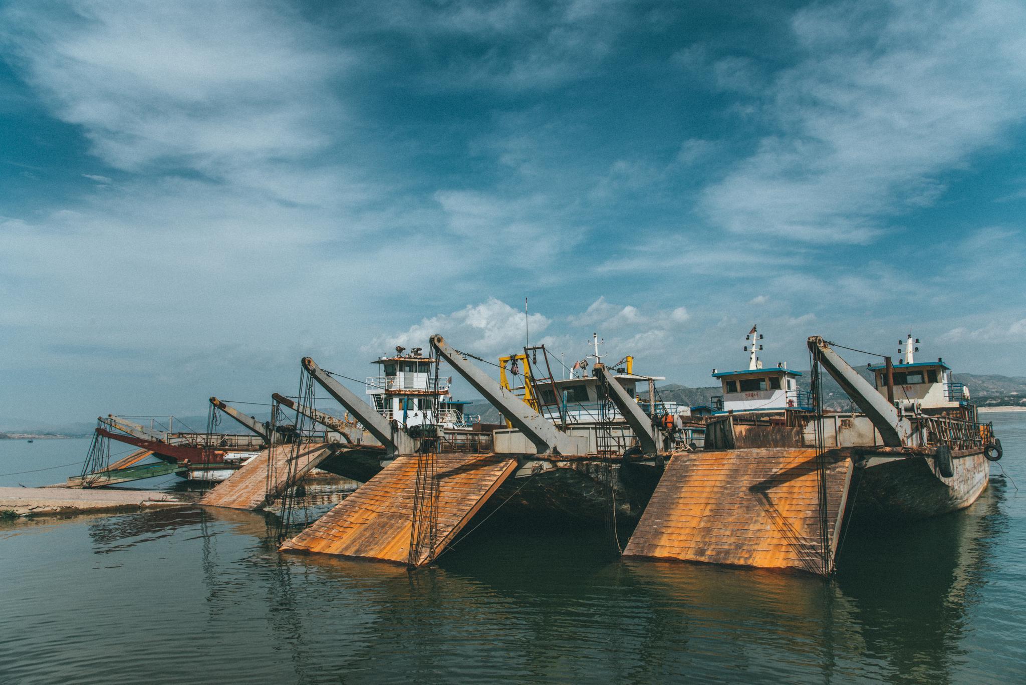 黄河刘家峡水库旁的停船,有一艘是废弃的大船,船身遍满时间的痕迹