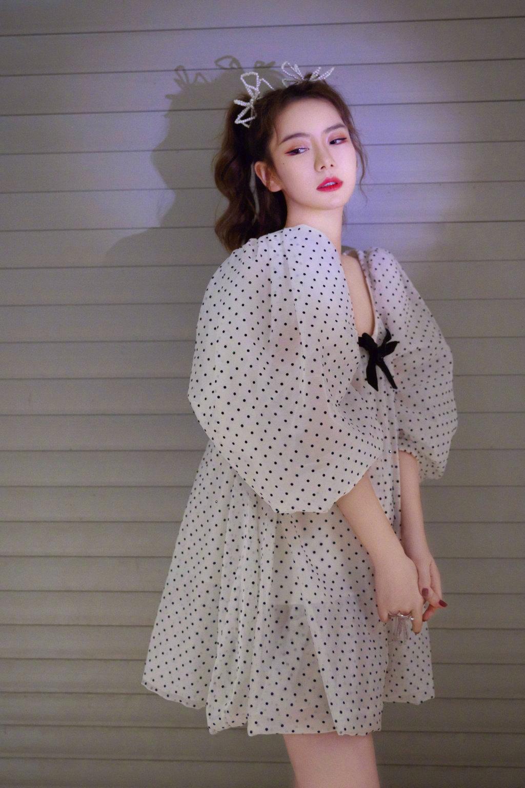 戚薇穿着轻盈的白色波点裙,梳起蝴蝶结双马尾