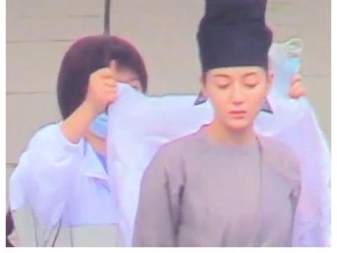 热巴片场拍戏,助理举着伞跟随给她披外套,手中拿着的口罩引热议