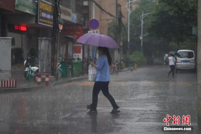 6月18日下昼,云南省昆明市突降暴雨,市民冒雨出行。中新社记者 刘冉阳 摄