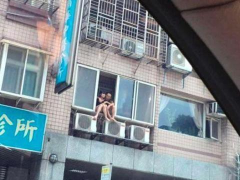 小两口坐在2楼窗户上,大家都以为他们要跳楼,结果却让路人羞红