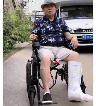 潘长江左脚粉碎性骨折,瘫坐轮椅难以行动,仍旧继续坚持拍戏