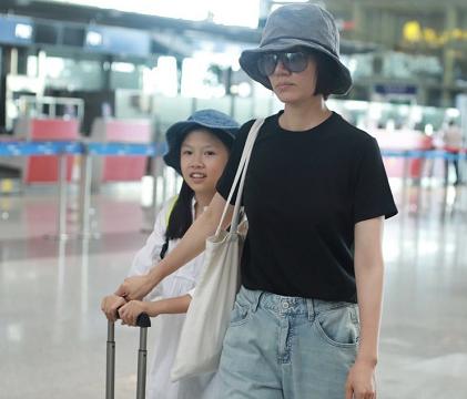 袁泉带女儿走机场,黑T恤配牛仔裤简约利落,女儿气质不输妈妈