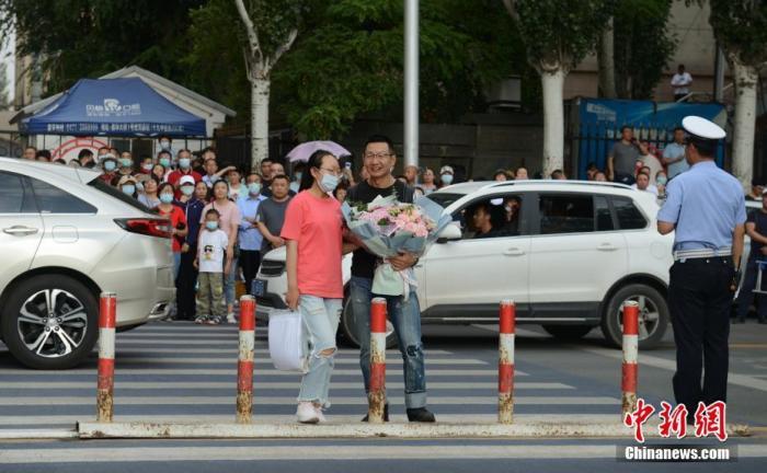 7月8日,内蒙古呼和浩特市一高考考点,考生结束考试后收到来自家长的鲜花。 中新社记者 刘文华 摄