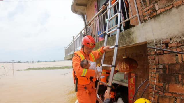 3个月大婴儿被洪水围困 消防员一手扶梯一手抱娃 轻手轻脚完成救