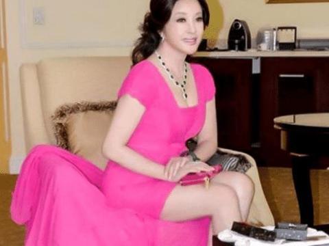 刘晓庆越老越妖艳,玫红长裙秀大长腿,坐下来却很尴尬