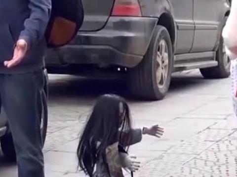 """街头恶搞:姑娘在路边发现""""奇异""""娃娃,好奇用手机拍照"""