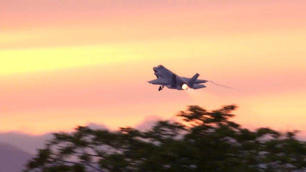 三沢空军场站,战机在金色阳光的沐浴下滑向跑道的场景……