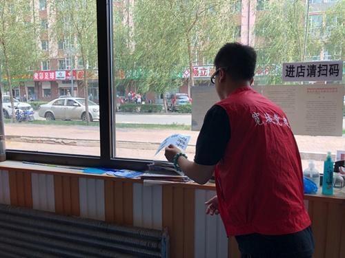首山路社区志愿者集中清理门店橱窗广告 美化市容街景