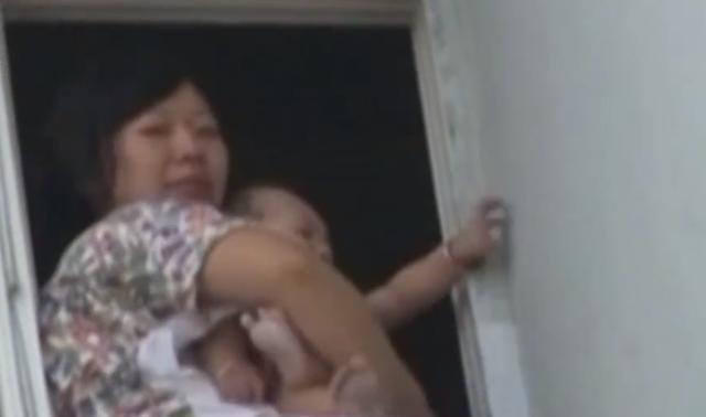 年轻妈妈因为家暴抱着孩子坐在窗边,丈夫:我喝了点酒!零容忍!