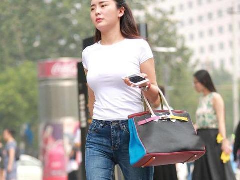 街拍:白色背心搭配小脚裤,美女一脸闷闷不乐是咋回事?