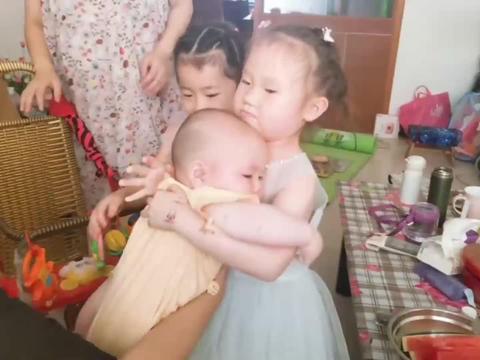 小四月和姐姐前后轮流抱小宝,大宝抱小宝,居然还穿上了小宝衣服