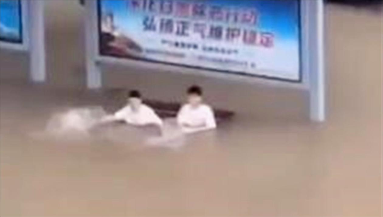 台风过境街道上积水严重 俩小伙泡水中等公交 还伸手比划着泳姿
