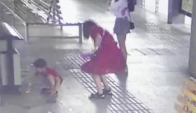 郑州公交站内小男孩一个人捡起垃圾桶外别人丢的碎纸片