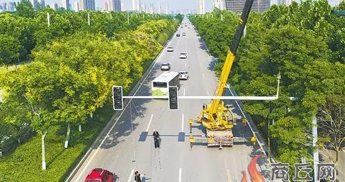 施工人员在丁字路口安装交通信号灯