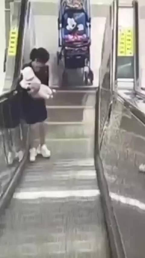 女子抱婴儿上扶梯眼看就要仰面摔倒……