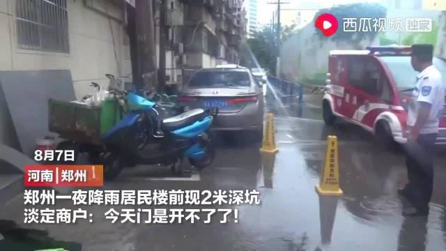郑州一夜降雨居民楼前现2米深坑,淡定商户:今天门是开不了了