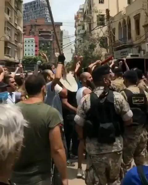 贝鲁特街头,一群示威者高喊口号,要求政府下台